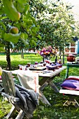 A table laid in a garden under apple trees