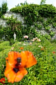 Flowers in garden of monastery Gerode with sculpture in distance, Germany