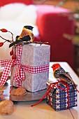 Verpackte Weihnachtsgeschenke mit Ziervögeln dekoriert