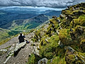 Rear view of a person sitting on rock in Snowdonian National Park, Wales, UK