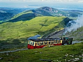 People travelling in train at Snowdonian National Park with mountain ranges, Wales, UK