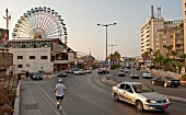Cars and people on street with ferries wheel in background at Luna park, Beirut, Lebanon