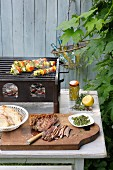Grilled lamb on a wooden board and cheese and vegetable skewers on a barbecue