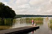 Children standing at dock near Breiter Luzin lake, Germany