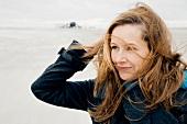 Frau im Wintermantel an der frischen Luft, zerzauste Haare