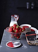 An arrangement of strawberries in a glass bowl next to old notebook