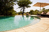 Woman sitting at pool in Forest Lodge, South Africa