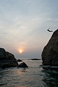 Person diving from rocks in sea at sunset, Sri Lanka