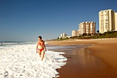 Woman in red bikini walking in water at beach at Umhlanga, South Africa