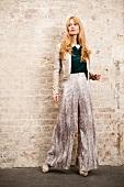 Frau in gemusterter Marlenehose aus Seide und Kunstlederjacke