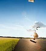 Man in air while doing kite surfing, backlit, Tempelhof-Schoneberg, Berlin, Germany