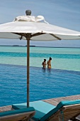 View of footbridge with umbrella and two women in sea, Anantara Dhigu island, Maldives