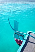 Boat in turquoise sea at island Veliganduhuraa, Maldives