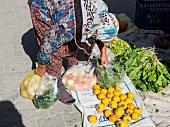 Woman picking up vegetables in weekly market in Yazikent, Aegean, Turkey