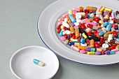Tablettenmix auf einem Teller, eine Tablette in einer kleinen Schale