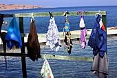 Swimsuit hanging on wooden pole by the sea in Turkbuku Peninsula, Golkoy, Turkey