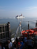 View of people at harbour and ferry in North Sea, Spiekeroog, Lower Saxony, Germany