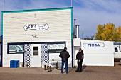 Two men standing in front of Deb's Country restaurant in Coronach, Saskatchewan, Canada