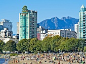Mountains, hotels and crowded English Bay Beach, Vancouver, British Columbia, Canada