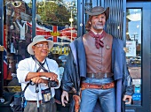 Tourist standing by the cowboy figure in Gastown, Vancouver, British Columbia, Canada