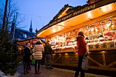 People at Christmas market stall at Lubeck, Schleswig Holstein, Germany