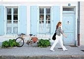 Women walking on street passing through house, Ile de Re, France