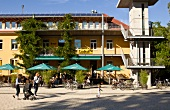People sitting outside cafe of restaurant Alfred Doblin-Platz in Vauban, Freiburg, Germany