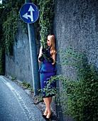 blonde Frau im eleganten blauen Kleid lehnt an einer Mauer, Straße