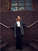 Frau steht an einer Hauswand, Fassade, im langen Abendkleid