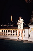 Frau posiert vor Eiffelturm, nachts, Promenade, in Felljacke, Minirock