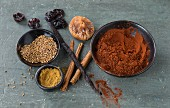An arrangement of cocoa powder, cinnamon, vanilla pods, dried fruit and anise