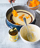 Mandarin marble cake being made – mandarins being scattered on top of the cake mix