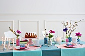 A table laid for a birthday with cake, candles and flowers in decorative vases