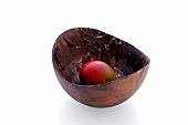 A fruit in a decorative wooden bowl