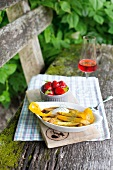 Vanilla asparagus and marinated strawberries on a bench outside