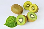 Green and yellow kiwis, whole and halved and with a leaf
