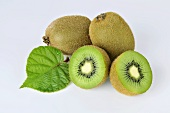 Green kiwis, whole and halved and with a leaf