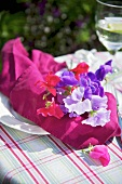 A place setting with a napkin and flowers on a garden table