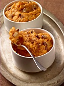 Two Bowls of Mashed Sweet Potato with Walnuts on a Metal Tray; One with Spoon