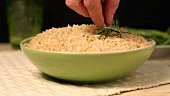 A bowl of rice being garnished with rosemary