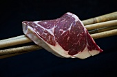 A Wagyu beef ribeye steak on bamboo sticks