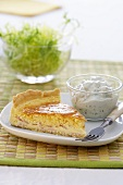 A slice of quiche Lorraine with a quark dip