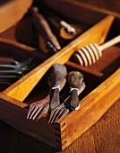 Old Wooden Spoons and Forks with Old Tools in a Wooden Box