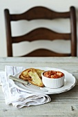 A tomato and crab meat dip with toasted bread on a table