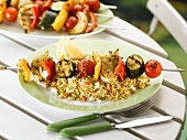 A vegetable kebab on a bed of couscous