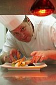 Chefkoch serviert Garnelen auf Avocadotatar mit Dip