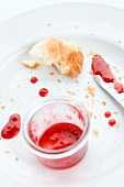 The remains of a croissant and jam on a plate