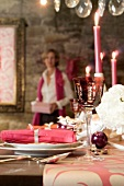 A table laid for Christmas dinner decorated in pink and a woman in the background with a present