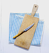 A knife and a chopping board on a cloth