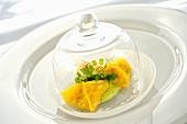 Ravioli mit Königskrabbenfüllung unter Glasglocke auf Glasteller